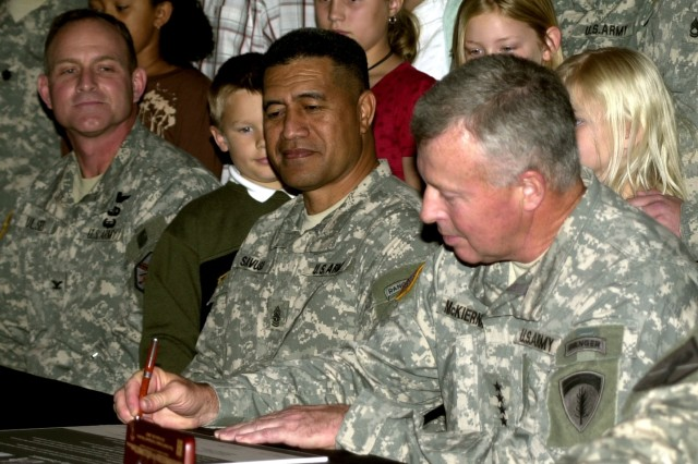 U.S. Army Europe Commander Gen. David McKiernan signs the Army Family Covenant in a ceremony on Campbell Barracks in Heidelberg, Germany Oct. 26. USAREUR Command Sgt. Maj. Iuniasolua T. Savusa (center) and Col. Robert J. Ulses, the U.S. Army Garrison Heidelberg commander (left) also signed the document.