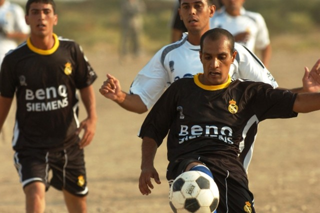 A policeman from the 2nd Battalion is pursued by one from the 1st Battalion during the championship soccer game between the two battalions from the 5th Brigade, 2nd National Police Division, at the National Police Academy in Numaniyah, Iraq, Oct. 21.