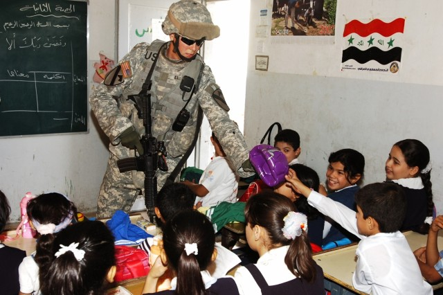 """1st Lt. Chris Gallion, a platoon leader with Company E, 1st Battalion, 5th Cavalry Regiment, passes out soccer balls to children at the Harthia Primary School in central Baghdad's Kindi neighborhood Oct. 23. Gallion's unit operates in central Baghdad attached to the 4th Squadron, 9th Cavalry Regiment, 2nd Brigade Combat Team, 1st Cavalry Division."""""""