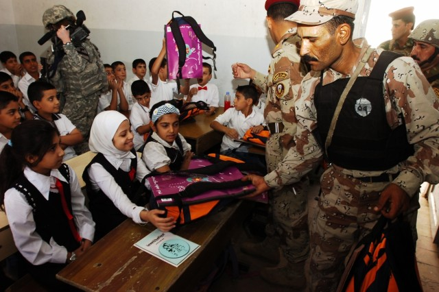 """An Iraqi army soldier passes out backpacks to children at the Harthia Primary School Oct. 23 in central Baghdad.Af'A,A The operation was conducted with members of Company E, 1st Battalion, 5th Cavalry Regiment."""""""