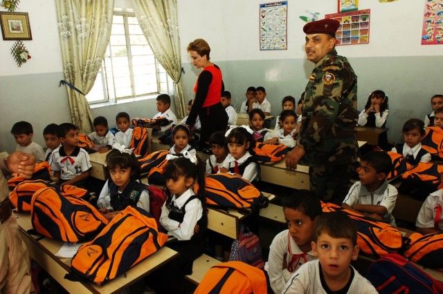A teacher at Harthia Primary School and an Iraqi Army soldier walk through a classroom after handing out backpacks to the students during a backpack drop Oct. 23 in central Baghdad's Kindi neighborhood.The operation was conducted by troops from Company E, 1st Battalion 5th Cavalry Regiment, which is attached to 4th Squadron, 9th Cavalry Regiment, 2nd Brigade Combat Team, 1st Cavalry Regiment.