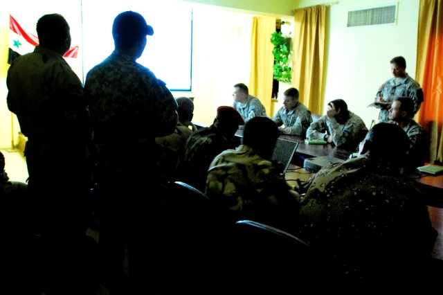 "Leaders from the 1st Battalion, 5th Cavalry Regiment, the Iraqi Army and a local volunteer group known as Forsan Al Rafideen, which is Arabic for ""knights of the river,"" share their common goals and knowledge of the battlefield at a synchronization meeting at Forward Operating Base Hawk in western Baghdad, Oct. 26"