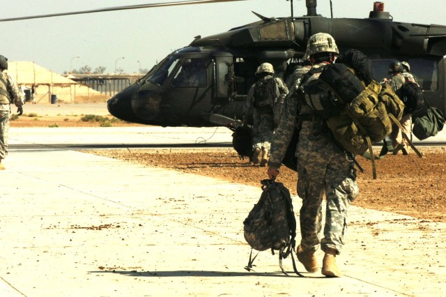 """With 15 months of medical evacuation missions behind them, Soldiers from Company C, 2nd """"Lobo"""" Battalion, 227th Aviation Regiment, 1st Air Cavalry Brigade, 1st Cavalry Division, load up their gear onto a UH-60 Black Hawk helicopter before they start their trip from Camp Taji, north of Baghdad, back to the United States Oct. 25."""