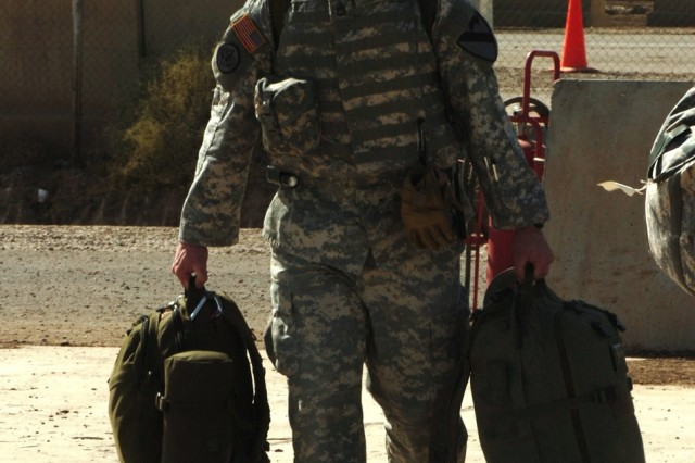 """Orchard Park, N.Y., native Sgt. 1st Class Jon Spiller, a flight medic for Company C, 2nd """"Lobo"""" Battalion, 227th Aviation Regiment, 1st Air Cavalry Brigade, 1st Cavalry Division, walks his gear to the waiting UH-60 Black Hawk helicopter at Camp Taji, Iraq, Oct. 25. Spiller, along with about 11 other Soldiers from Co. C, the medical evacuation unit for Baghdad, are headed home as part of the first contingent of troopers from the 1st ACB to redeploy back to the states. """"I really think we made a difference over here. We helped out the best we could. I'll be happy when everybody gets home,"""" Spiller said."""