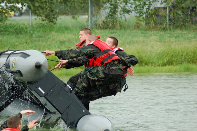 Soldiers from the Indiana Army National Guard participate in water survival and operational training at a lake in Evansville, Ind. Here, they are attempting to board their overturned Zodiac boat.