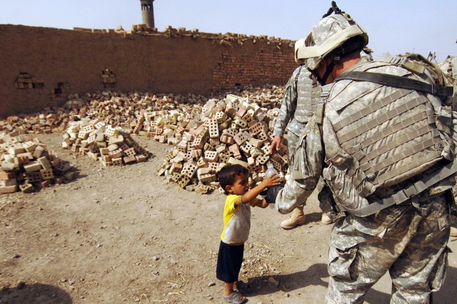 A Soldier gives an Iraqi boy his bottle of water.