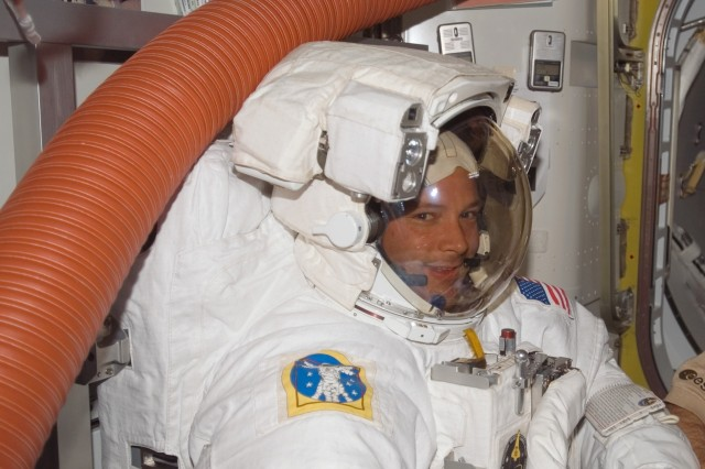 Attired in his Extravehicular Mobility Unit  spacesuit, Army astronaut Doug Wheelock, STS-120 mission specialist, prepares for the mission's first session of extravehicular activity in the Quest Airlock of the International Space Station while Space Shuttle Discovery is docked with the station. ""