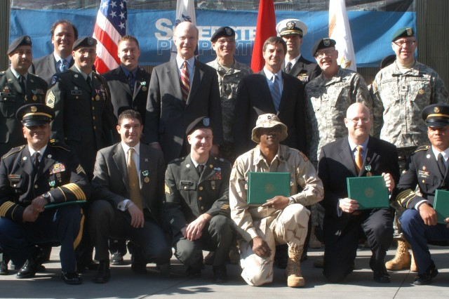 The Honorable Pete Geren, Secretary of the Army (center) and Department of Defense General Counsel, the Honorable William J. Haynes, pause for a photo with the 13 Soldiers awarded for their service as first responders immediately following Sept. 11, 2001 attacks in New York.