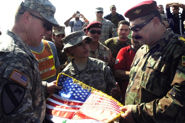 Huntsville, Ala., native, Lt. Col. Dale Kuehl, commander of the 1st Battalion, 5th Cavalry Regiment, presents Iraqi Army Lt. Col. Wail Mohamed Hussain, commander of the 2nd Battalion, 1st Brigade, 6th Division Iraqi Army, with a gift in appreciation of their cooperation in the Ameriya neighborhood of Baghdad's Al Mansour District at the end of a soccer tournament at Camp Liberty Oct. 28. The tournament was part of a larger get-together, including a cookout hosted by 1-5 Cav., which operates in Ameriya attached to the 2nd Brigade Combat Team, 1st Infantry Division.