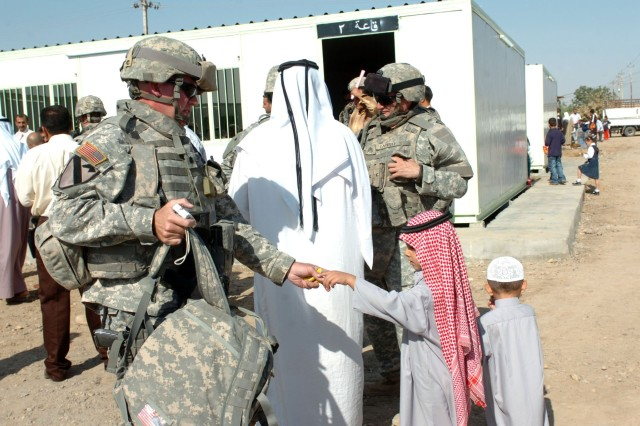 Lt. Col. Michael Donaher, commander, Company A, 492nd Civil Affairs Battalion, hands out treats to the children at the school opening in Al Awad, Iraq Oct. 29.""