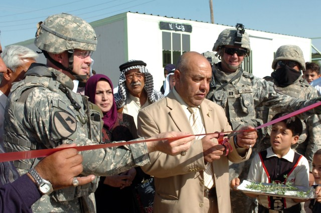 Ali Abid Abbas, the education committee chairman for the Taji Qada cuts the ribbon signifying the opening of the temporary school built in Al Awad, Iraq for the local and surrounding area children Oct. 29.""