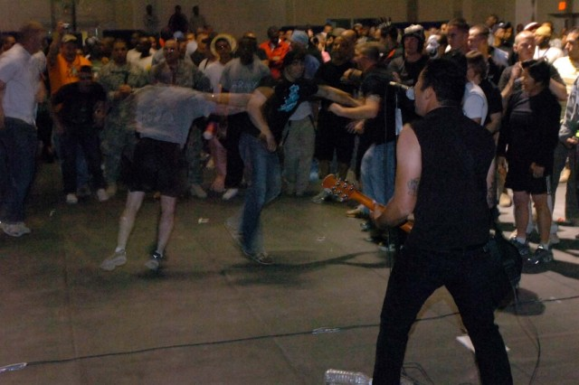 """Lead singer and guitarist of the band Madison Avenue, Pfc. Samuel """"Gonzo"""" Gonzalez, Jr., of the 571st Military Police Company, attached to 3rd Brigade Combat Team, 1st Cavalry Division, performs melodic emo songs for a dancing crowd of Soldiers Halloween night at Salie Gym, Forward Operating Base Warhorse."""