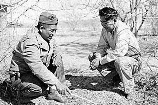 "Sergeant Sinew L Riley is teaching his son, Larrie H. Indian wood lore. Ft. Huachuca, Arizona, 1942."""