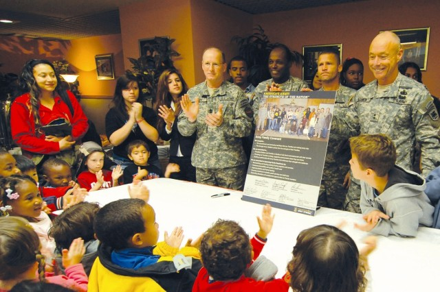 CASERMA EDERELE, Italy - Surrounded by Army Families for which it is written, Maj. Gen. Frank Helmick, Southern European Task Force commander, displays the Army Family Covenant he had just signed Nov. 2 with Col. Virgil Williams, U.S. Army Garrison Vicenza commander, and their respective command sergeants major, Command Sgt. Maj. Earl Rice and Command Sgt. Maj. Keith Filipp. The covenant is a document introduced by the secretary of the Army and the Army chief of staff stating the Army\'s commitment to caring for Soldiers and their families. The signing ceremony included a briefing about the many programs and funding the Army has already brought to the Vicenza military community, and the showing of the Army Family video.