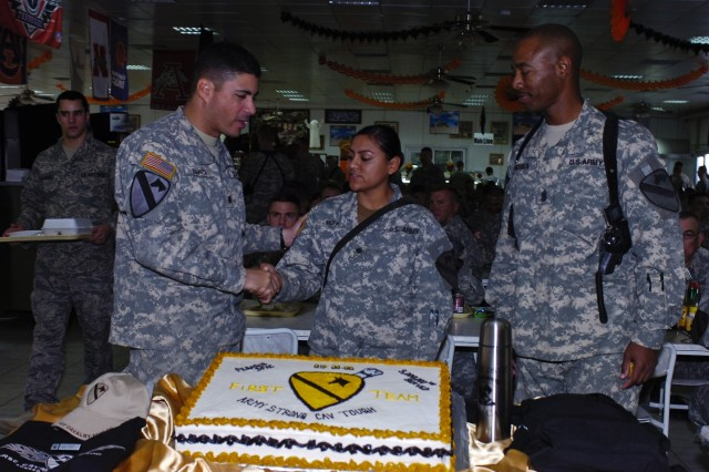 Killeen, Texas native Spc. Diana Mota (center), Headquarter Support Company, Division Special Troop Battalion, 1st Cavalry Division, is congratulated by her battalion commander, Lt. Col. Daniel R. García (left), and Command Sgt. Maj. Jeffery Moses, the battalion's top noncommissioned officer, for being the three millionth customer of the Pegasus Sports Oasis dining facility at Camp Liberty in western Baghdad, Oct. 27.
