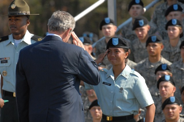,President George W. Bush returns salute to a graduating Soldier with the 3rd Battalion, 34th Infantry Regiment after presenting her an award during Friday's ceremony.