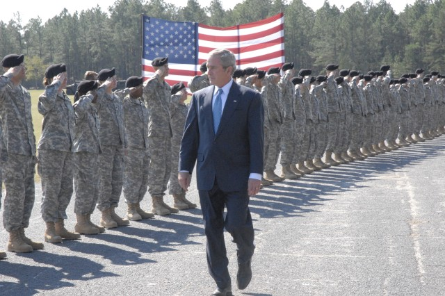 Fort Jackson Soldiers salute President George W. Bush as he walks onto the graduation field at Fort Jackson Friday