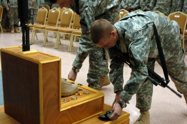 Placing their 1st Cavalry Division patches on a memorial, Soldiers from the 3-8 Combined Arms Battalion, 3rd Brigade Combat Team, 1st Cavalry Division pay respects to their fallen comrade, Cpl. Adam Chitjian, at Logistical Support Area Anaconda, Oct. 31.