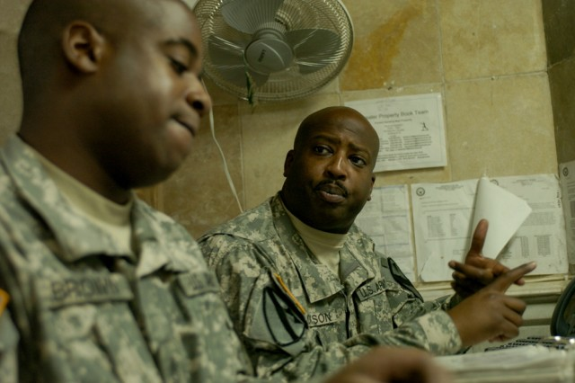 """Shreveport, La., native Staff Sgt. Jessie Jackson Jr. (right), Headquarters and Headquarters Troop, 4th Squadron, 9th Cavalry Regiment, 2nd Brigade Combat Team, 1st Cavalry Division, helps Philadelphia native Sgt. 1st Class James Brown, also from HHT, 4-9 Cav., with a hand receipt in the """"Boom Boom Room"""" on Forward Operating Base Prosperity in central Baghdad."""