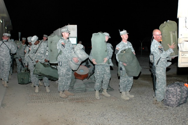 "Soldiers from the 1st Air Cavalry ""Warrior"" Brigade, 1st Cavalry Division, load their bags up on a truck at Camp Taji, Iraq, before they begin their wait for their flight to head home Oct. 31. This group of troopers will set up the units' footprint in the states to ensure a smooth transition for their comrades when they redeploy."