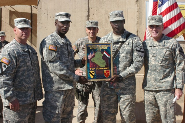 Soldiers from Battery B, 1st Battalion, 82nd Field Artillery Regiment to include Leander, Texas native 1st Sgt. Tim Keesling; Hampstead, N.Y. native Capt. Leighton Anglin, Battery B commander, and the battery's retention noncommissioned officer, Sgt. Demotriz Brooks, a native of Biloxi, Miss. receive the 1st Cavalry Division's top company award for retention from Maj. Gen. Joseph F. Fil, Jr. (right), commanding general, Multi-National Division-Baghdad and 1st Cavalry Division and Command Sgt. Maj. Philip F. Johndrow (center), 1st Cav. Div. command sergeant major, during a ceremony on Camp Taji, Iraq Nov. 1. Battery B accomplished 400 percent of its retention mission for Fiscal Year 2007 with 36 reenlistments but had a mission of only nine. Fil said the event marked the first time that a 1st Cavalry Division retention award has been presented at the company level.