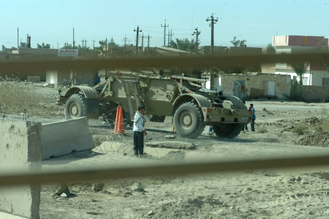 As seen through the window of a Buffalo mine resistant vehicle, an Iraqi boy holds onto concertina wire that he has pulled off a road so vehicles in a U.S. convoy can pass near Hor Al Bosh, Iraq Nov. 2 during a mission by Soldiers from the 1st Brigade Special Troops Battalion to clear nearby roads of improvised explosive devices.