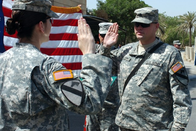 Capt. Michelle Ramos administers the oath of enlistment to Staff Sgt. Brian Fulton during a reenlistment ceremony Sept. 12 at Forward Operating Base Prosperity in central Baghdad.