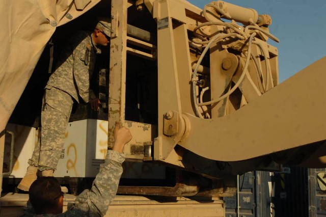 Spc. Adamm Creel, Headquarters and Headquarters Company, attached to Co. D, 1-12 Combined Arms Battalion, 3rd Brigade Combat Team, 1st Cavalry Division, works with his buddy to lift supplies into a shipping container as they prepare for redeployment from Baqouba, Iraq, Nov. 4.