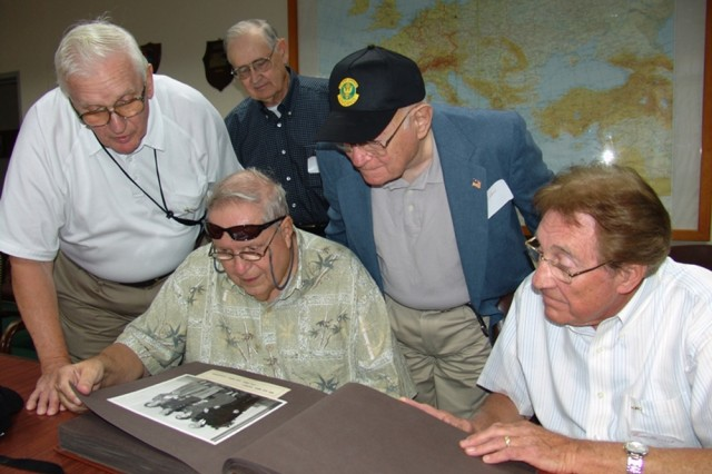Joe Mularski, left standing; Edgar Tingley, back row; Ed Napoleoni, sitting with scrapbook; Goldye Levi; and Al Fritsch look through a Camp Darby photo album from the 1950s.