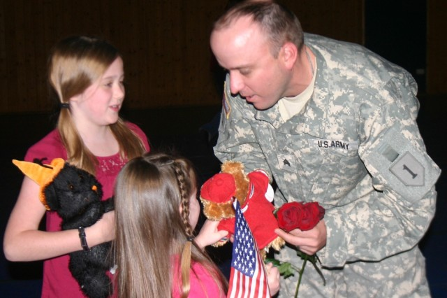 Bailey, left, and Isabell brought roses for their dad, Sgt. Scott Olson, to welcome him home from a 15-month deployment with Task Force 1-26.