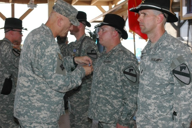 "Lt. Gen. Raymond Odierno, commanding general of Multi-National Corps-Iraq, (left) presents the Distinguished Flying Cross to Onawa, Iowa, native Chief Warrant Officer Elliott Ham, (second from right), as Portage, Ind., native Chief Warrant Officer 4 Steven Kilgore, (right), waits in a ceremony Oct. 28 at Camp Taji, Iraq. Four Apache pilots from 1st ""Attack"" Battalion, 227th Aviation Regiment, 1st Air Cavalry Brigade, 1st Cavalry Division, earned Distinguished Flying Crosses for their actions against five gun trucks with heavy machine guns on May 31. The Distinguished Flying Cross is the U.S. military's highest aviation-specific award."