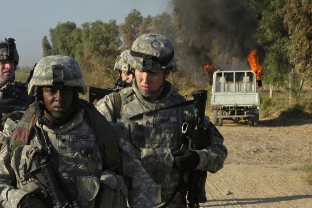 Spc. Billy Cassis, Sgt. Brandon Dean and other Soldiers from the 4th Stryker Brigade Combat Team, 2nd Infantry Division, Task Force Iron, walk away from an insurgent vehicle they torched near an insurgent safe house south of Hussein Hamadi village, Iraq, during Operation Ultra Magnus.