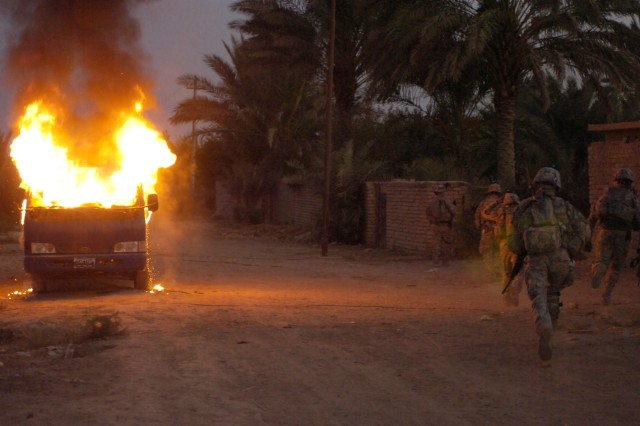 Soldiers from the 4th Stryker Brigade Combat Team, 2nd Infantry Division, Task Force Iron, from Fort Lewis, Wash., along with Iraqi Army soldiers run by a burning vehicle in Hussein Hamadi village, Iraq during Operation Ultra Magnus.