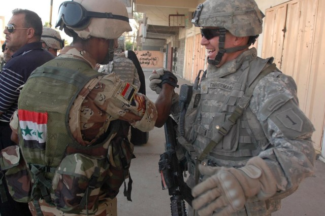 Maj. Eric Timmerman, operations officer for U.S. Army Europe's 1st Battalion, 18th Infantry, greets an Iraqi Army soldier in southern Baghdad's Rashid District, Oct. 4, 2007. The 1-18th 'Vanguards' are currently wrapping up their