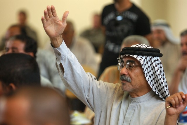 A man raises his hand to ask a question during the first-ever town hall meeting held in a recently-renovated school in Karkh Oct. 31. The meeting was held for residents to discuss concerns with local leaders and officials.