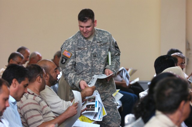 Capt. Gene Palka, 4th Squadron, 9th Cavalry Regiment's fire support officer, hands out fliers with information regarding reconciliation efforts and an upcoming job fair to attendees of a town hall meeting in Karkh Oct. 31. This was the first time a meeting of this type was held for residents to discuss concerns with local leaders and government officials.