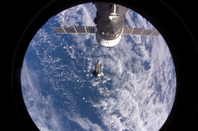 Space Shuttle Discovery after it undocked from the International Space Station Nov. 5 at 5:32 a.m. The Russian spacecraft docked to the station is visible at top.