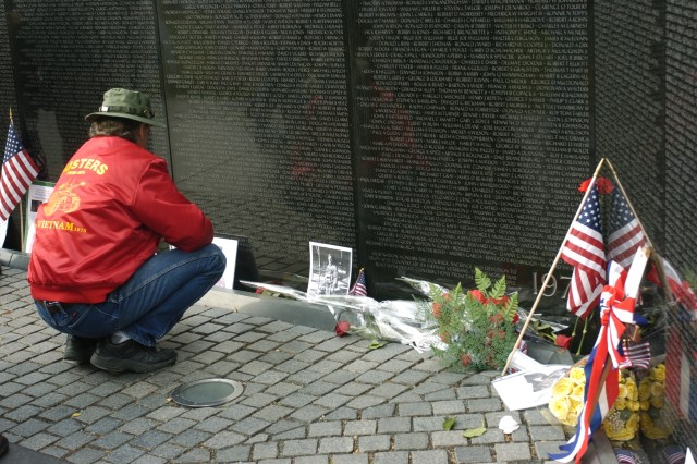 A Vietnam Veteran pauses after locating a name on the Vietnam Veterans Memorial Wall.