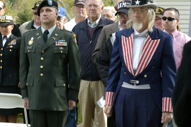 Lt Col Jon Grigorian, maneuver branch chief, Fort Monroe, VA and Dana L. Trudelle as Uncle Sam, stand with other veterans honored during the Veterans Day Celebration in Yorktown, VA, Nov 12.