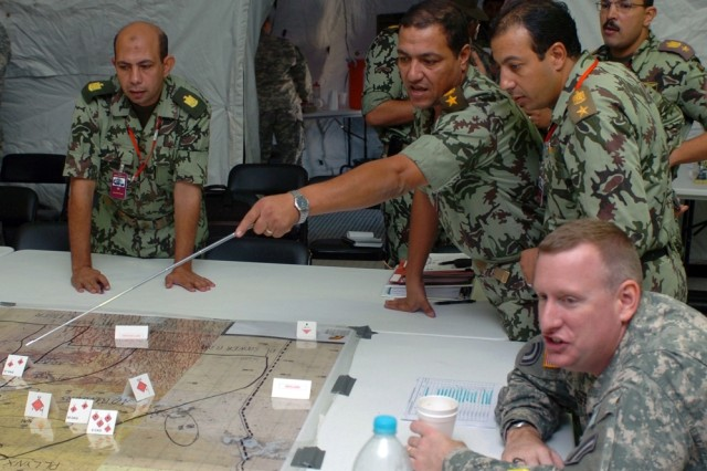 Lt. Col. Hesham Rashdy (center), chief of Intelligence for the Egyptian 9th Armored Division, reviews battle plans with his division staff and the 42nd Infantry Division Chief of Staff Col. Carl Pfeiffer.