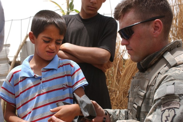Sgt. Matthew Ashmead, a medic with the 25th Infantry Division, measures the forearm of a boy for a splint, during a patrol near Tounis, Iraq.