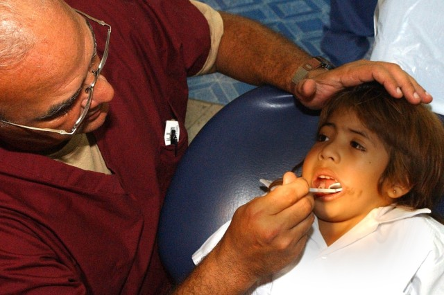 Lt. Col. Manuel Marien, a pediatric dentist from Fort Hood, Texas, examines the teeth of a Honduran child during a medical readiness training exercise in Tegucigalpa, Honduras.