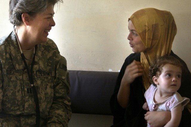 Capt. Jan Rose, from the 12th Cavalry Regiment, provides treatment and consultation for an Iraqi family in the village of Tahrir.