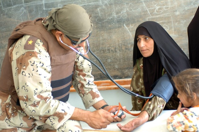 An Iraqi Army doctor from 3rd Brigade, 6th Iraqi Army, assesses an Iraqi women's health during a combined medical effort with the Fires Squadron, 2nd Stryker Cavalry Regiment, attached to 1st Brigade Combat Team, 1st Cavalry Division, in Horse Village, Iraq, Nov. 7.  The Soldiers treated 170 Iraqis with minor ailments.