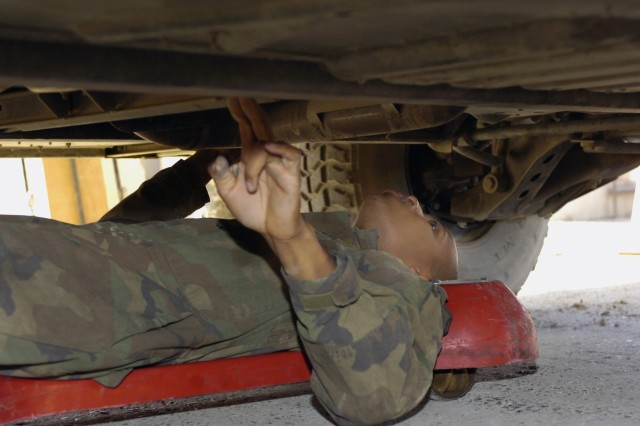 New Orleans native, Spc. Joshua Lummings, a light wheel mechanic with the Headquarters Support Company, Special Troops Battalion, 1st Cavalry Division, checks for damage on the bottom of an unarmored humvee in the dispatch lane of the STB motor pool at Camp Liberty in western Baghdad Nov. 6.