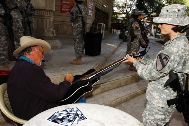 "Pvt. Stacey Hanson has her guitar signed by ""The Singing Cowboy,"" Freddie Fuller, a Saledo, Texas native who performed at Forward Operating Base Prosperity in central Baghdad for Soldiers of the 2nd Brigade Combat Team, 1st Cavalry Division"