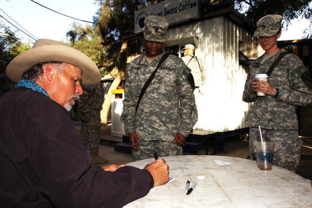 """Freddie Fuller, a Saledo, Texas native who goes by the name, """"The Singing Cowboy,"""" signs an autograph for Sgt. 1st Class Angela Parker, while Staff Sgt. Ludmila Walsh looks on, after a performance for Soldiers of the 2nd Brigade Combat Team, 1st Cavalry Division at Forward Operating Base Prosperity in central Baghdad Nov. 10."""