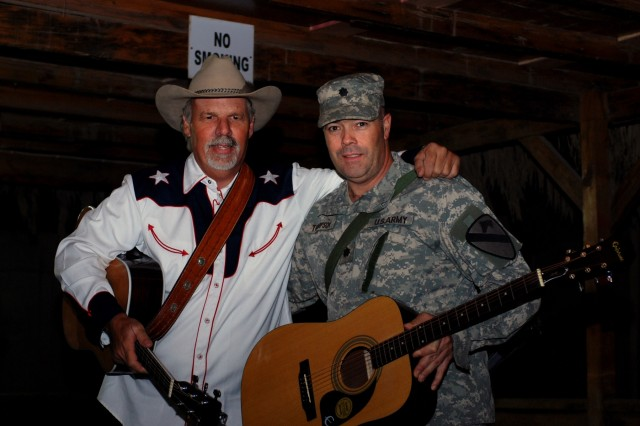 """Potlatch, Idaho native, Lt. Col. Greg Thompson, an operations officer for Multi-National Division - Baghdad and the 1st Cavalry Division, receives a guitar at the end of a concert by Freddie Fuller, the """"Singing Cowboy,"""" at the Pegasus Dining Facility at Camp Liberty in western Baghdad Nov. 12. Fuller, a Salado, Texas native, drew Thompson's name out of a box audience members had put their names in before the concert."""