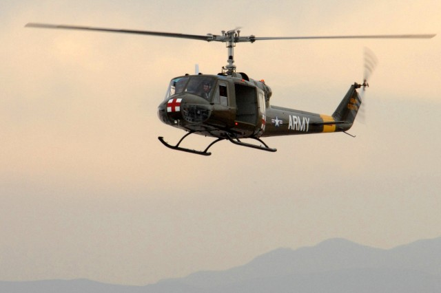 A Vietnam-era UH-1 Huey helicopter prepares to land to pick up a role-playing downed pilot.