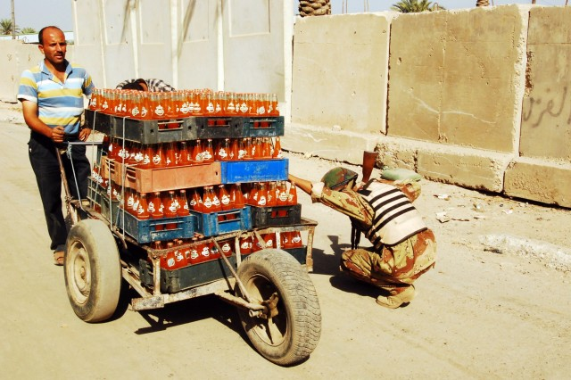 A local merhcant waits while an Iraqi Army soldier inspects his hand truck packed with soft drinks at a checkpoint in the western Baghdad Ameriyah neighborhood, Nov. 9.